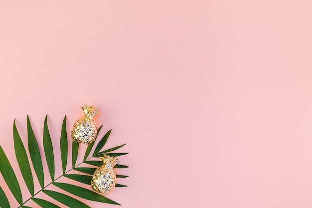 Creative flat lay top view of green tropical palm leaves millennial pink paper background with pineapples copy space