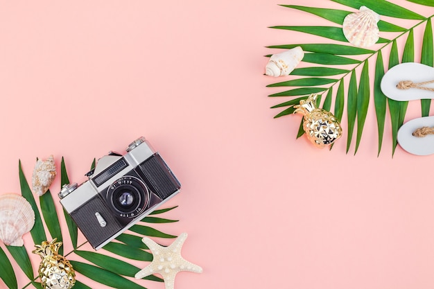 Creative flat lay top view of green tropical palm leaves and old photo camera on millennial pink paper background with copy space. minimal tropical palm leaf plants summer travel concept template