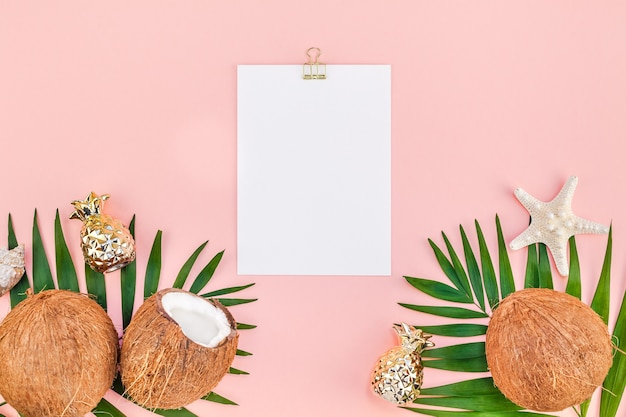Творческий плоский вид сверху макет зеленых тропических пальмовых листьев кокосы чистый лист бумаги розовая открытка клип доска фон копией пространства. шаблон концепции летних путешествий с минимальными тропическими пальмовыми листьями