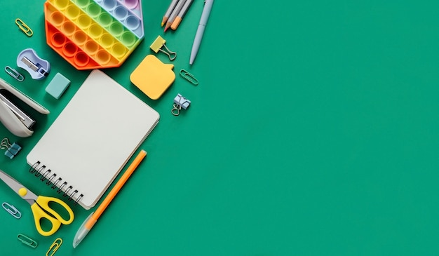 Творческий плоский вид сверху канцелярских принадлежностей на фоне зеленой бумаги. снова в школу концепции. скопируйте шаблон пространства для текста или дизайна