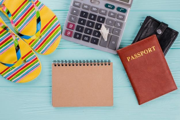 여권, 슬리퍼, 계산기가 포함된 창의적인 평면 여행 컨셉입니다. 베이지색 수첩을 분실했습니다.