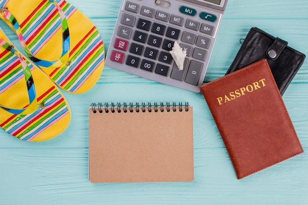 Creative flat lay travel concept with passport, flip-flops and calculator. ãâ¡losed beige notebook.