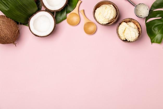 Креативная плоская планировка с кокосовым мороженым и тропическими растениями на розовом фоне