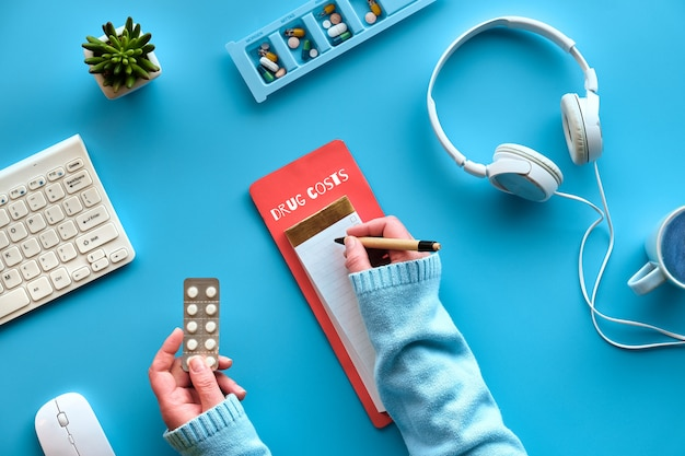 Creative flat lay with pen and calculator in hands to calculate drug costs. keyboard, calculator, pills and pill case on mint blue wall. checking costs or vitamins, drugs, food supplements.