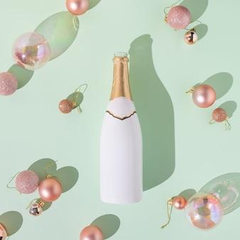 흰색과 금색 샴페인 병 및 민트 녹색 표면에 대한 크리스마스 장식으로 크리에이티브 플랫 누워