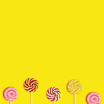 Creative flat lay with with sweet round candy lollypops with stripes on stick on yellow