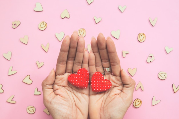 Creative flat lay of woman's hands with two hearts on pastel background.