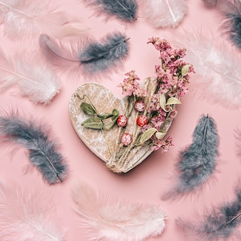 Creative flat lay of wooden heart with natural plants and feather.