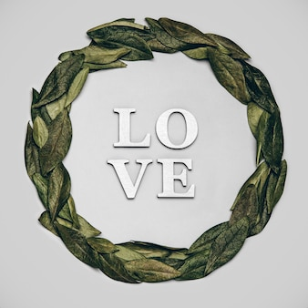 Creative flat lay of word love on grey background with natural leaves.