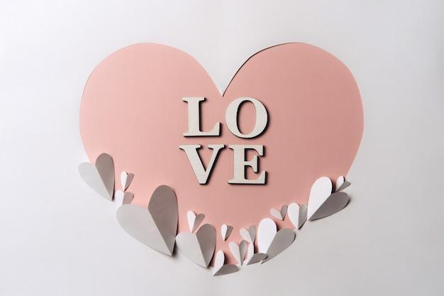 Creative flat lay of word love on heart shaped