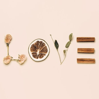 Creative flat lay of word love made with natural leaves, flowers, lemon and cinnamon