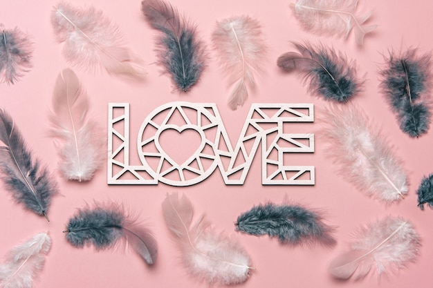 Creative flat lay of word love with natural feather.