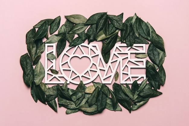 Creative flat lay of word love with natural leaves.