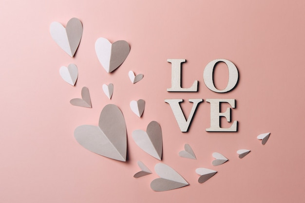 Creative flat lay of word love with paper hearts.