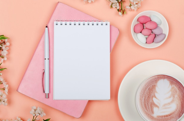 Creative flat lay of workspace desk, notepad and lifestyle objects on pink background