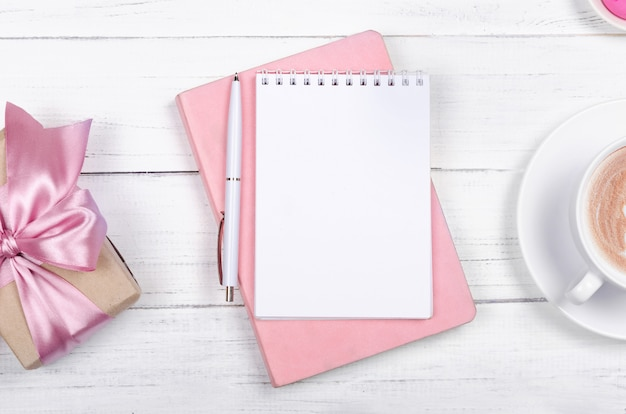 Creative flat lay of workspace desk, notepad and lifestyle objects on wooden background