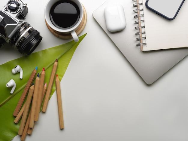 Креативное плоское рабочее пространство с камерой, смартфоном, кофейной чашкой, принадлежностями, местом для копирования и листом, украшенным на столе
