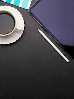 Creative flat lay workspace with digital tablet, stylus pen, coffee cup and copy space on black desk