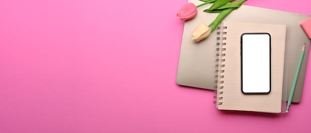 スマートフォンの文房具のラップトップとピンクの背景にスペースをコピーするクリエイティブなフラットレイワークスペース