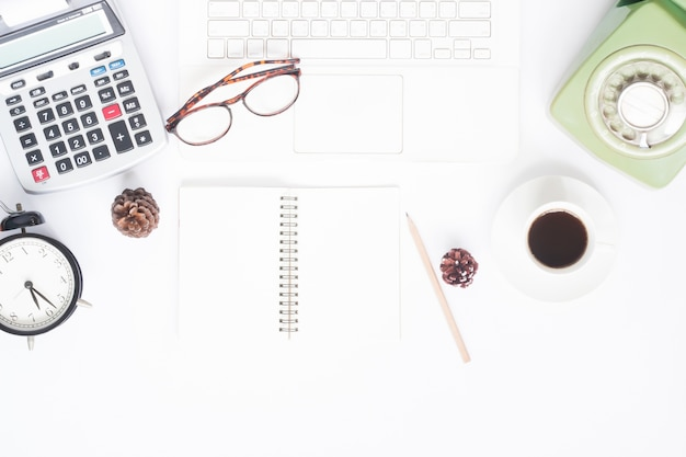 Creative flat lay of workspace with white laptop, retro style telephone, coffee cup and blank notebook for text