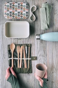 Creative flat lay, zero waste lunch concept with set of reusable wooden cutlery, lunch box, drinking bottle and reusable coffee cup. sustainable lifestyle top view, flat layout on aged wood.