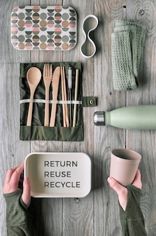 Creative flat lay, zero waste lunch concept with set of reusable wooden cutlery, lunch box, drinking bottle and reusable coffee cup. sustainable lifestyle top view, flat layout with text on wood.