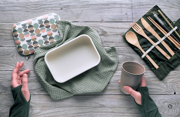 Creative flat lay, zero waste lunch concept with set of reusable wooden cutlery, lunch box, drinking bottle and reusable coffee cup. sustainable lifestyle top view, flat layout on wood, copy-space.