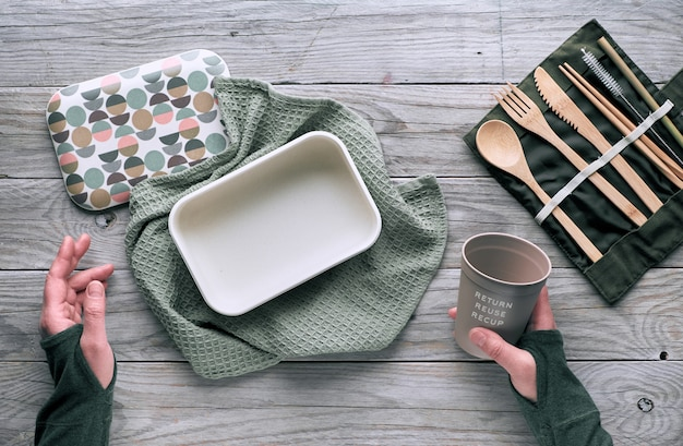 Creative flat lay, zero waste lunch concept with set of reusable wooden cutlery, lunch box, drinking bottle and reusable coffee cup. sustainable lifestyle top view, flat layout on wood, text space.