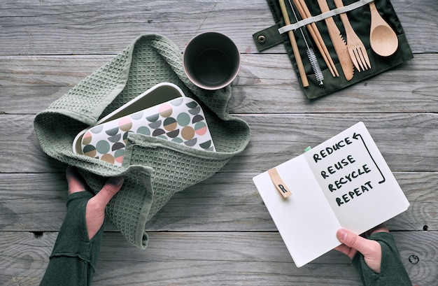 Creative flat lay, zero waste lunch with set of reusable wooden cutlery, lunch box in cotton cloth and reusable coffee cup. sustainable lifestyle, text
