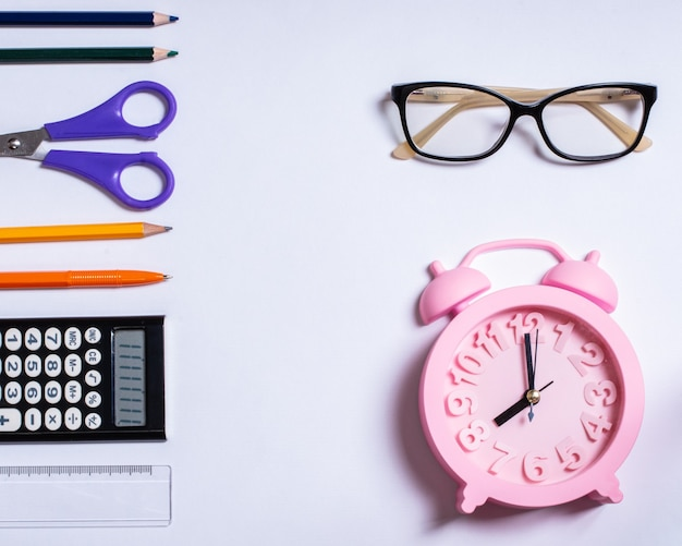 Creative flat top view of standing back to school concept, summer time, education concept. colored school supplies, glasses and pink alarm clock on a white background, copy space, design