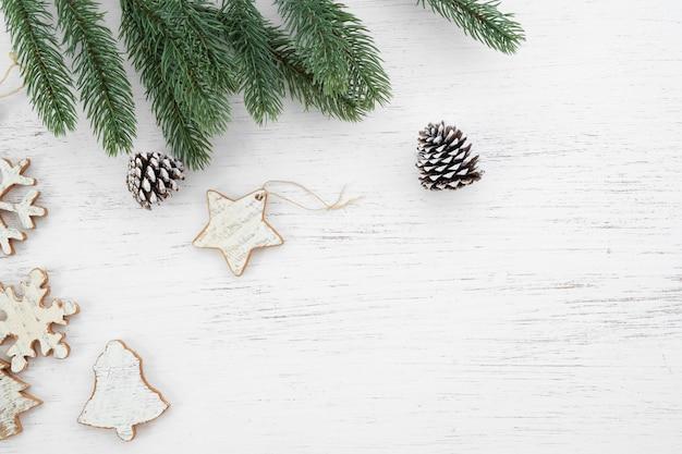 Рождественские листья ели фона и простоватые элементы, украшающие на белом деревянном столе. creative flat макет и вид сверху композиция с границей и копией пространства дизайна.