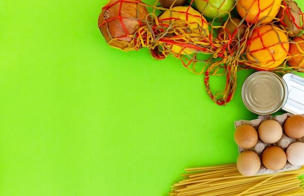 パントリーの主食と創造的なフラットレイ。パスタ、卵、果物、缶詰。緑の背景に基本的な製品の上面図