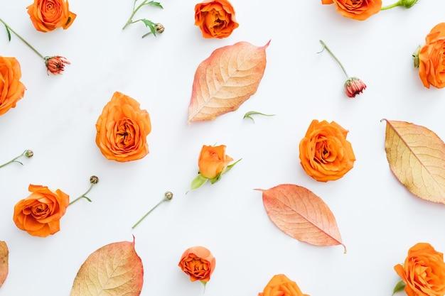 Креативная цветочная композиция осенние листья и оранжевые розы на белом