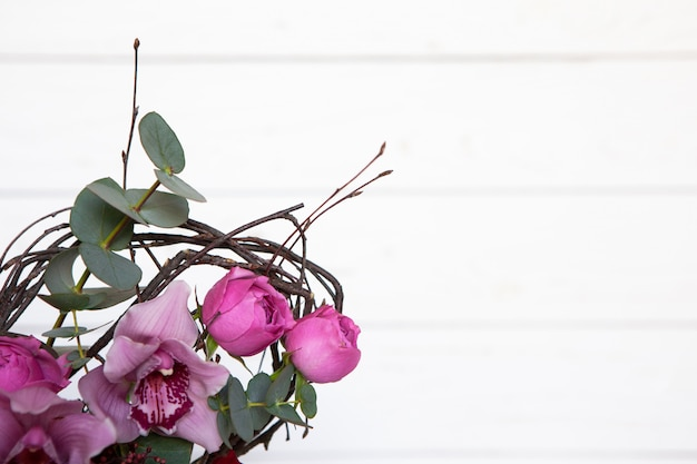 Creative flower bouquet on white wooden background. focus on flowers, background is blurred