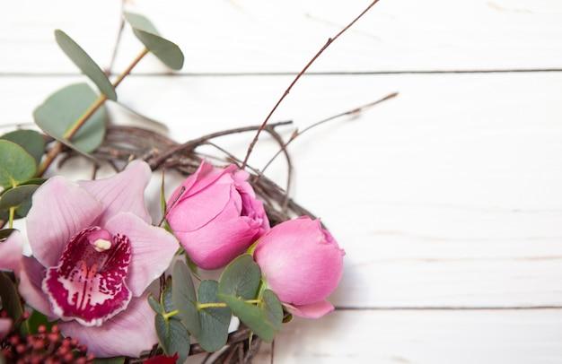 Creative flower bouquet on white wooden background.