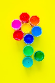 A creative flower made up of jars of paint on a yellow background with a place for text vertical pho...