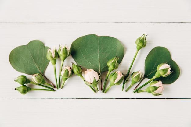 創造的な花と葉の構成。フラットレイ、白い背景。ピンクのバラと花柄。