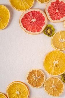 Креативная еда фруктовая текстура с сушеным грейпфрутом, киви, апельсином и лимоном, вид сверху белая стена