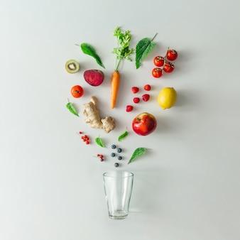 Креативный макет еды с фруктами, овощами и листьями на яркой мраморной стене стола с чашкой чая. концепция минимального здорового напитка. плоская планировка.