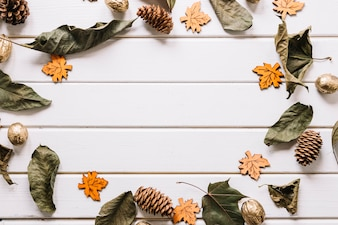 Creative frame composition with leaves and pine cones