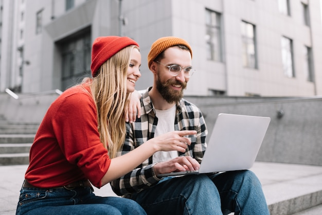 Creative freelancers planning startup project using laptop computer. smiling and positive hipsters working together, woman shows a finger on display