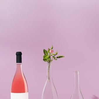 ロゼワインボトルとピンクのバラで作られたクリエイティブな正面パターン。パステル紫の背景。自然やアルコールの夏の飲み物の概念。