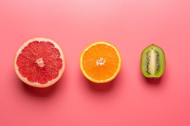 濃い影とピンクの背景に創造的な果物の構成