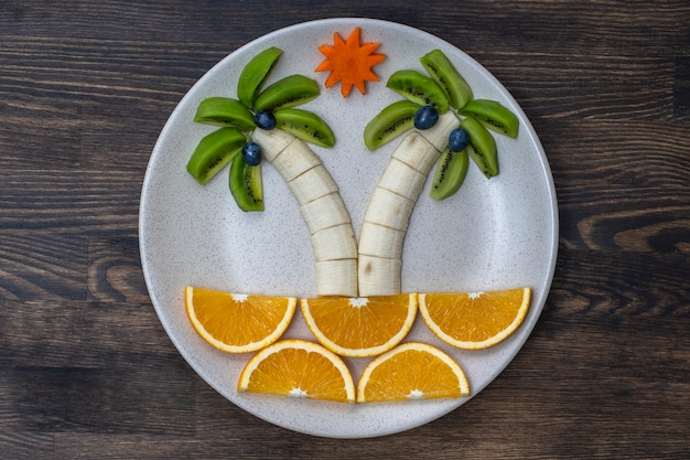 キウイ、バナナ、ブドウ、にんじん、オレンジを使ったクリエイティブなフルーツデザート。コンセプトの子供たちの食べ物。子供のための楽しくて健康的なフルーツサラダ。木製のテーブルの上の白いプレートの果物から作られたヤシの木の形