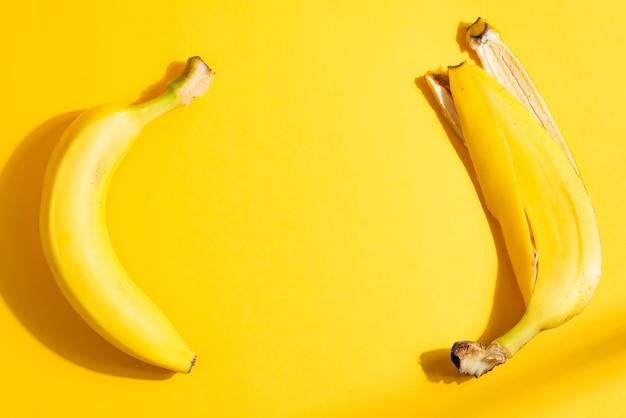 熟した新鮮な黄色のバナナから創造的な果物のフレームとハードシャドウ、コピースペースと同じ色の背景に皮をむきます。上面図。ベジタリアンの健康食品の概念。