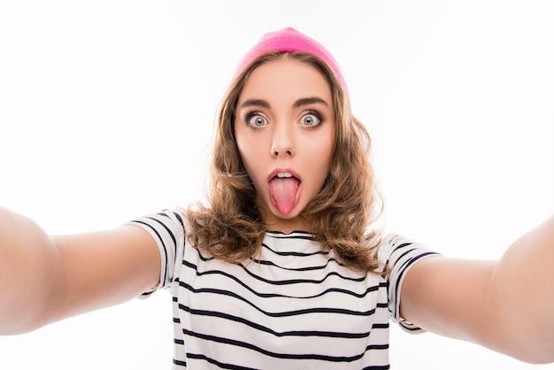 Креативная смешная девушка в розовой шляпе делает комическое селфи