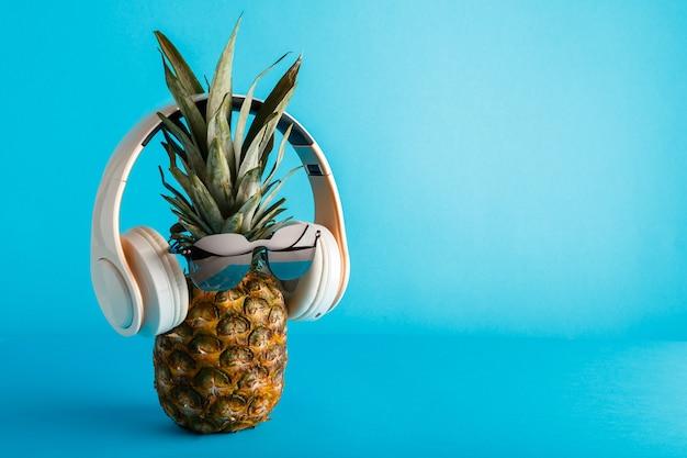 선글라스 헤드폰을 착용하는 창조적 인 재미 파인애플 얼굴. 파란색 여름 배경 복사 공간에 음악을 듣고 뜨는 서핑 파인애플 얼굴. 고품질 재고 사진.