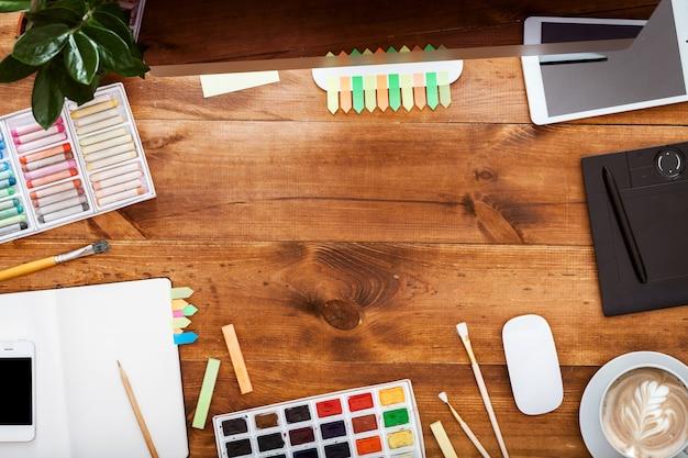 創造的なグラフィックデザインワークステーションコンセプト、茶色の木製の机の上のコンピューターの塗料