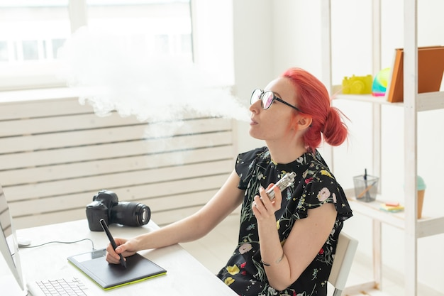 Creative, graphic designer, people concept - young creative woman smoking a vape while working in a graphic tablet.