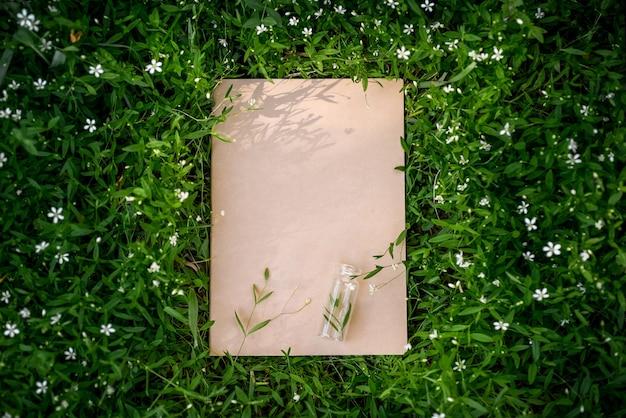 自然の葉と牧草地の草の創造的な緑の花の背景。クラフト紙フレーム。